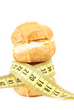Concept of slimming, caramel cakes with measuring tape Stock Image