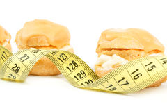 Concept of slimming, caramel cakes with measuring tape Stock Photography