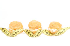 Concept of slimming, caramel cakes with measuring tape Stock Photos