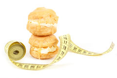 Concept of slimming, caramel cakes with measuring tape Royalty Free Stock Images