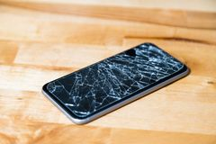 Concept of smart phone with broken screen. Top view on wooden desk background. Cracked, shattered lcd touch screen on modern. Cellphone. Gadget needs repairing stock image