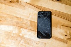 Concept of smart phone with broken screen. Top view on wooden desk background. Cracked, shattered lcd touch screen on modern royalty free stock image