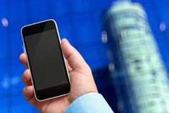 Smartphone in hand with a blank area to insert a custom image. Modern building on background. Concept of Smartphone in hand with a blank area to insert a custom royalty free stock images