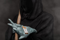 The concept: smoking kills. Angel of death holding cigarette. The concept: smoking kills. Grim reaper holding cigarette. Studio shot over black background royalty free stock images