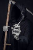 The concept: smoking kills. Grim reaper holding cigarette Royalty Free Stock Image