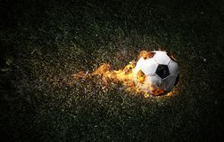 Soccer Ball on Fire. Concept of soccer game with ball in fire flames. Mixed media royalty free stock image