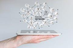 Concept sociaal netwerk om vrienden, families en globaal aantal arbeidskrachten te verbinden De tablet van de handholding of slim stock foto's