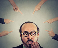Concept social accusation of guilty businessman fingers pointing at him. Concept of social accusation of guilty businessman many fingers pointing at him  on grey Royalty Free Stock Images