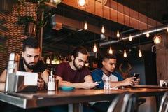 Concept social de dépendance de media Amis de métis regardant leurs téléphones dans la barre de salon Photographie stock