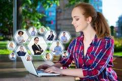 Concept social de réseau - adolescente s'asseyant avec l'ordinateur portable dans le pair Photos libres de droits