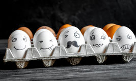 Concept social networks communication and emotions - eggs wink. On dark wooden background Royalty Free Stock Photos