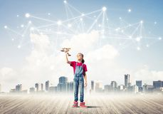 Concept of social wireless connection and internet use for commu. Cute little girl is launching a wooden plane, dream about sky Stock Image
