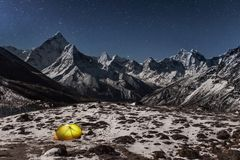 Concept of solitude and freedom in the wild. Night winter camping in the mountains. Lonely tent lit up from inside in the valley under Ama Dablam mountain on a Stock Photography