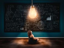 The concept of solving a math formula. Young girl looking up to a lightbulb in front a blackboard full of formulas . The concept of solving a math formula royalty free stock photography