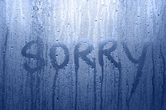 Concept sorry word message on the wet window. Conceptual sorry word handwritten message on the rainy glass window background. Blue color tone used Royalty Free Stock Photo