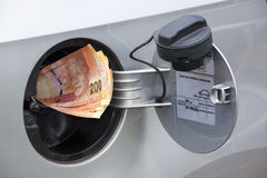 Concept South African Banknotes Feeding Into Petrol Tank. Concept of south african banknotes feeding into petrol tank indicating petrol price increase stock photo