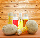 Concept of spa compress balls with bottles of aroma oil on woode Royalty Free Stock Photography