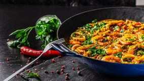 Concept of Spanish cuisine. Paella with seafood, shrimps, squid and greens, cooked in wok pan on street. street food. The concept of Spanish cuisine. Paella with royalty free stock photography