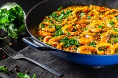 Concept of Spanish cuisine. Paella with seafood, shrimps, squid and greens, cooked in a wok pan on street. street food. Concept of Spanish cuisine. Paella with royalty free stock photography