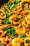 Concept of Spanish cuisine. Paella with seafood, shrimps, squid and greens, cooked in a wok pan on the street. street food. The concept of Spanish cuisine royalty free stock images