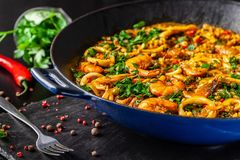 Concept of Spanish cuisine. Paella with seafood, shrimps, squid and greens, cooked in a wok pan on the street. street food. The concept of Spanish cuisine stock image