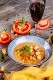 Concept of Spanish cuisine. Tomato soup Gazpacho from fresh tomatoes. Beautiful serving dishes in a blue plate on a wooden table. In a restaurant. background stock photos