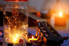 Concept of sparklers in Glass jar with some of the guitar. On blurred light candle burning  background Stock Photo
