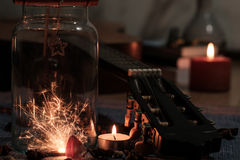 Concept of sparklers in Glass jar with some of the guitar. On blurred light candle burning  background Royalty Free Stock Images