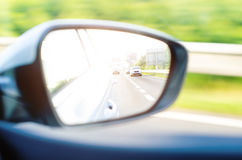 Concept of speed. Car driving on the road. Reflection in a car mirror.Rear view mirror reflection. Blurry background. Stock Photography