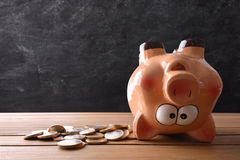 Concept of spending the savings with piggy bank upside down. And blackboard background. Horizontal composition. Front view Royalty Free Stock Images
