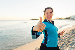 Concept of sport, fitness, healthy lifestyle and running - Motivated sporty woman doing thumbs up success gesture after. Outdoors workout at the beach royalty free stock image