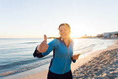 Concept of sport, fitness, healthy lifestyle and running - Motivated sporty woman doing thumbs up success gesture after Stock Photos