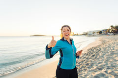 Concept of sport, fitness, healthy lifestyle and running - Motivated sporty woman doing thumbs up success gesture after. Outdoors workout at the beach Royalty Free Stock Photos