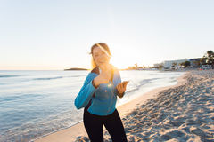 Concept of sport, fitness, healthy lifestyle and running - Motivated sporty woman doing thumbs up success gesture after. Outdoors workout at the beach Stock Photography