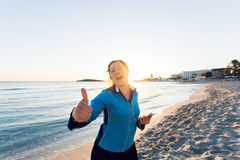 Concept of sport, fitness, healthy lifestyle and running - Motivated sporty woman doing thumbs up success gesture after. Outdoors workout at the beach Stock Photo