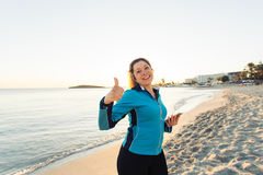 Concept of sport, fitness, healthy lifestyle and running - Motivated sporty woman doing thumbs up success gesture after. Outdoors workout at the beach Stock Image