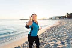 Concept of sport, fitness, healthy lifestyle and running - Motivated sporty woman doing thumbs up success gesture after. Outdoors workout at the beach royalty free stock images