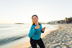 Concept of sport, fitness, healthy lifestyle and running - Motivated sporty woman doing thumbs up success gesture after Royalty Free Stock Image