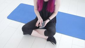 Concept of sport and fitness. Young sportswoman sitting and using fitness tracker and smartphone