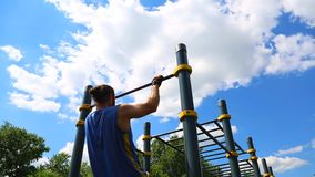 Concept sport motivations. Rear view of a muscular man pulled up on a horizontal bar outdoors on a sunny day. Athlete. Training outdoors, crossfit stock footage