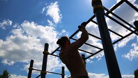 Concept sport motivations. Rear view of a muscular man pulled up on a horizontal bar outdoors on a sunny day. Athlete. Training outdoors, crossfit stock video