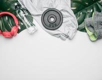 Concept sportenlevensstijl, sportkleding en toebehoren op een witte achtergrond, met fles van water en tropische bladeren wordt o royalty-vrije stock afbeeldingen