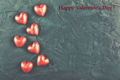 Valentine`s Day, First Love, Happiness of Love, Chocolate hearts. Concept: St. Valentine`s Day, First Love, Happiness of Love. Chocolate hearts on a black stone Stock Image