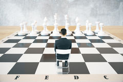 Concept of strategy chess. Strategy concept with sitting businessman and white chess pieces on huge chessboard with concrete wall in the background. 3D Rendering Royalty Free Stock Photo