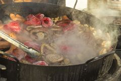 The concept of street food: vegetables and sausages grill, steam over a frying pan, blur.  stock images