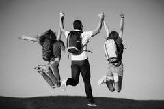 Concept succes Drie vrienden die op bergbovenkant springen op blauwe hemel stock foto