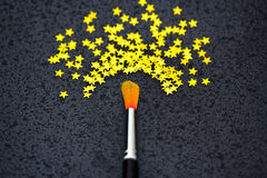 Concept of success: brush painting stars. Brush creating stars on black: uniqueness, talent Stock Images