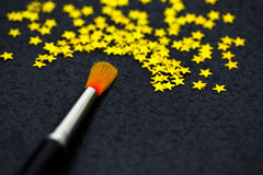 Concept of success: brush painting stars. Brush creating stars on black: uniqueness, talent Royalty Free Stock Image