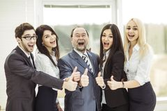 Concept of success in business: the boss and triumphant business team make the gesture thumbs up. Boss and triumphant business team make the gesture of thumb up Royalty Free Stock Image