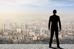 Concept of success with businessma. N standing on the roof and looking ahead for the opportunities. Rear view Stock Image